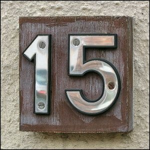 Wooden block with the number 15 on it posted on a wall